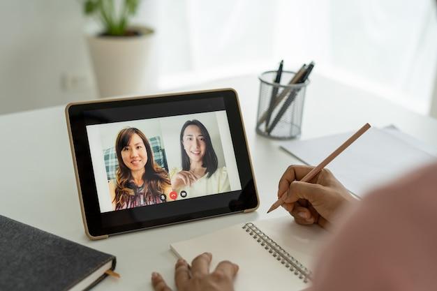 Азиатская бизнес-команда рассказала о планировании работы по видеоконференции. деловые люди используют подключение к интернету на планшете для онлайн-встреч в режиме видеоконференцсвязи.