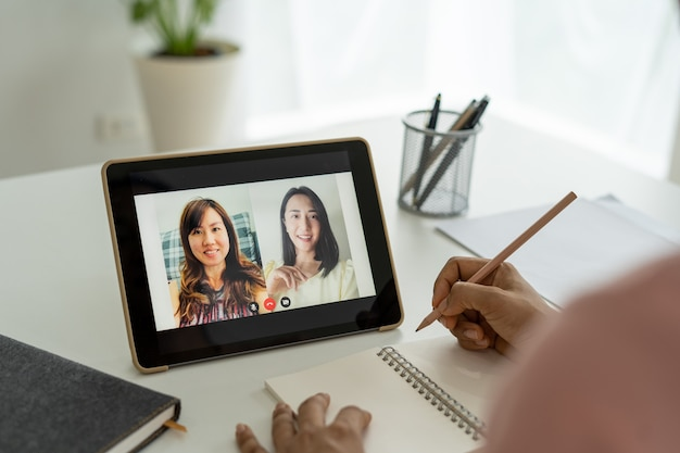 Asian business team talked about planning work for video conference. business people use a tablet connection internet for online meetings in video conferencing.