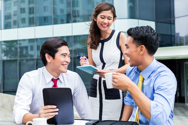 아시아 비즈니스 여자와 남자는 커피를 마시는 컴퓨터에서 외부 작업