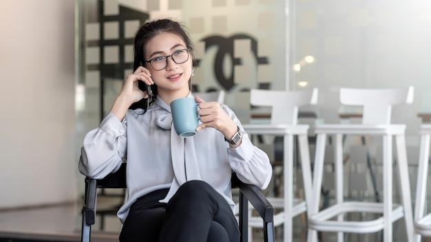Азиатские бизнес-леди с удовольствием пьют кофе и разговаривают по телефону в свободное время в офисе.