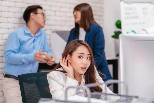 아시아 비즈니스 여성은 연인 문제에 대해 이야기하는 부부의 이야기를 듣고 호기심이 많습니다.