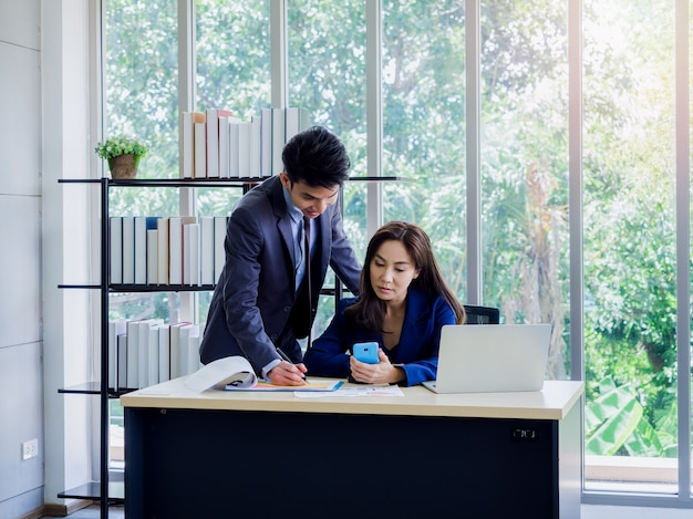 Asian business woman and businessman wearing suit working together in office