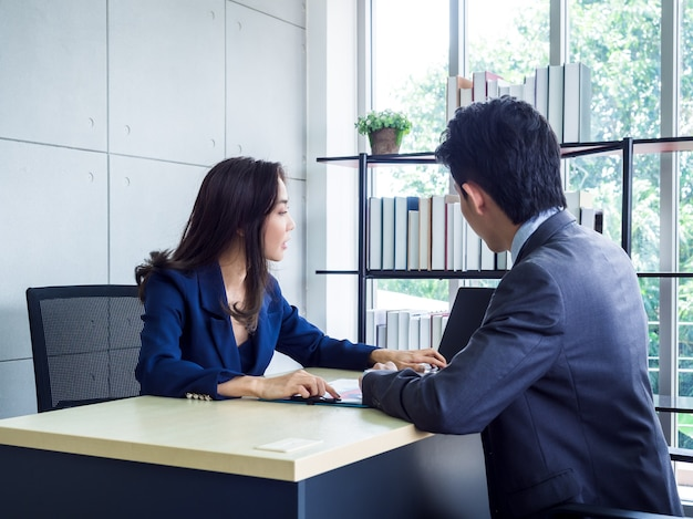Asian business woman and businessman working together in office