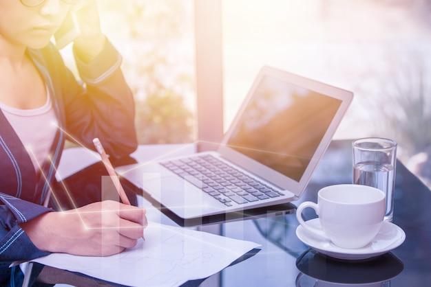 筆記用紙に書くことで呼び出すアジアのビジネス女性鉛筆を持っているタイのオフィスの女性