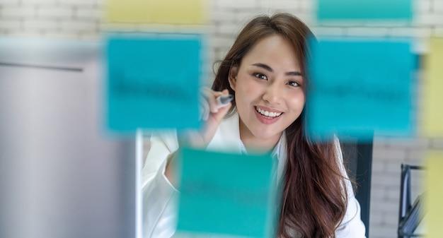 행복에 집중하고 그것을 거울에 게시하는 아시아 비즈니스 여자
