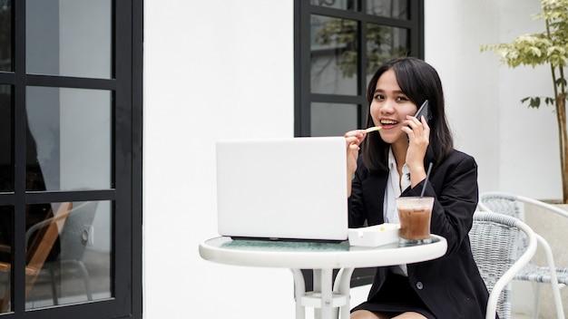 아시아 비즈니스 여자 먹고 카페에서 스마트 폰 이야기