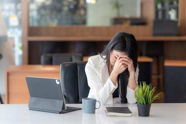 アジアのビジネスウーマン疲れた退屈な気持ちは、事務作業でよく考えることを強調しました。