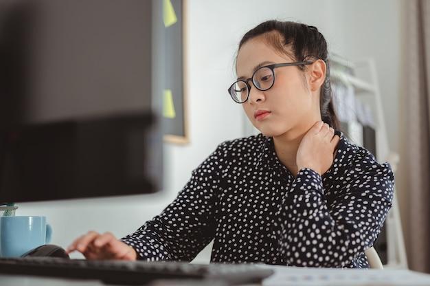 アジアのビジネスウーマンは、コンピューターを長時間使用し、オンラインで作業した後、首の痛みを感じます