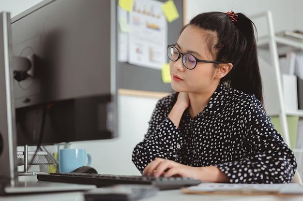 アジアのビジネスウーマンは長い間コンピューターで働いた後首の痛みを感じるビジネスウーマン