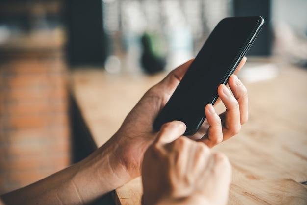 Азиатская рука бизнес-леди используя и касаясь умного телефона с белым пустым пустым экраном.