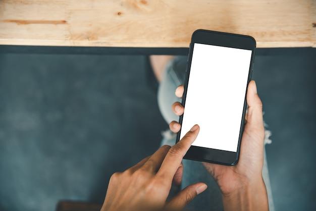 白い空白の空の画面でスマートフォンを使用して触れているアジアのビジネス女性の手。