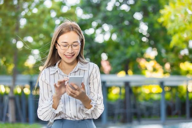 スマートフォン立っている公園屋外緑の自然の背景を見て幸せな笑顔アジアのビジネス女性