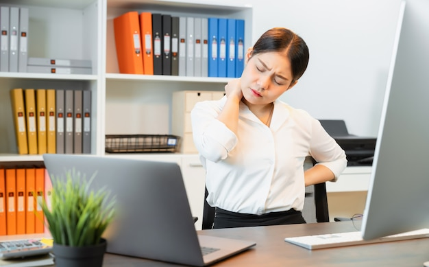 Asian business woman have a backache because sitting and working with using a computer for a long time. this may be the cause of office syndrome.