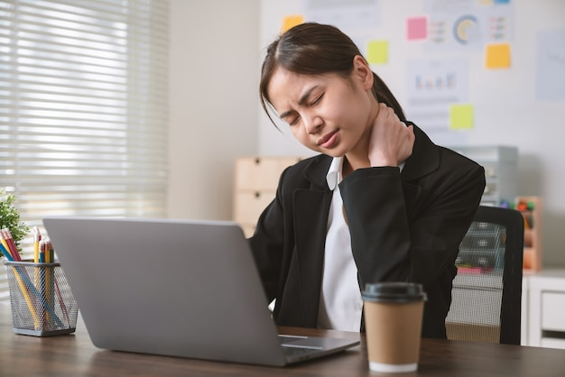 Asian business woman have a neck pain because using the computer and working for a long time at office.