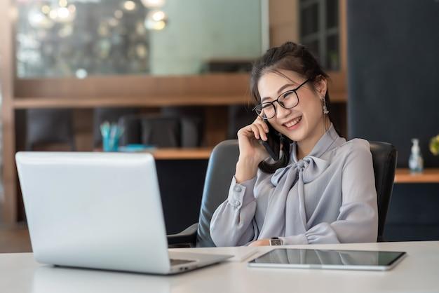 アジアのビジネスウーマンは、オフィスの机の上で電話、ラップトップ、タブレットで話す喜びを持っています。