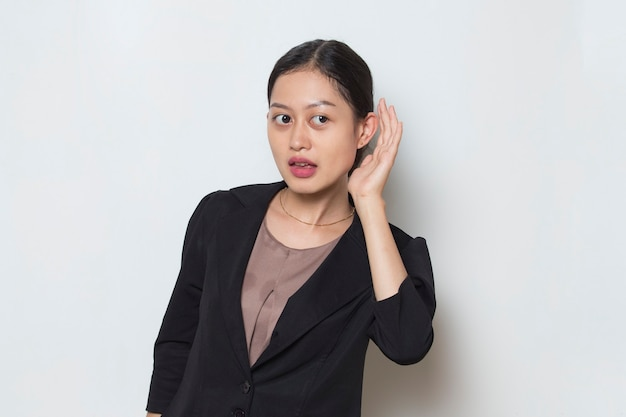 Asian business woman hold her hand near her ear and listening