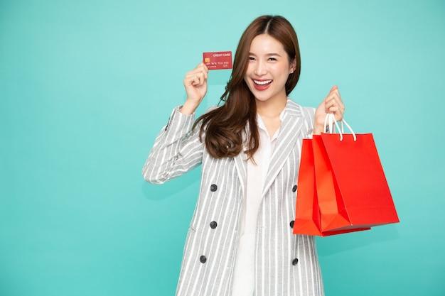 Азиатская деловая женщина, держащая кредитную карту и красные хозяйственные сумки с фестивалем китайского нового года, изолированным на зеленом фоне
