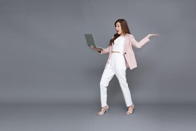 노트북 컴퓨터를 들고 있는 아시아 비즈니스 여성은 회색 배경에 격리된 와우라고 느낌