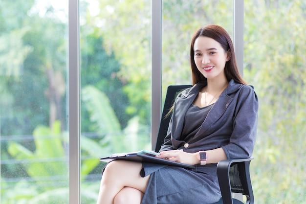 짙은 회색 드레스를 입은 아시아 비즈니스 여성은 사무실 의자에 앉아 행복하게 일합니다.