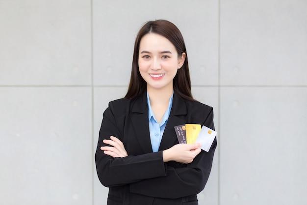 フォーマルな黒のスーツを着たアジアのビジネスウーマンが手にクレジットカードを持って見せます