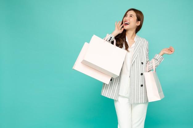 녹색 배경에 고립 된 밝은 녹색 쇼핑백을 들고 소송에서 아시아 비즈니스 여자