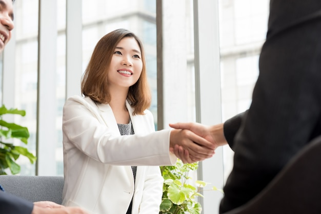 Asian business woman making handshake with client in office lounge