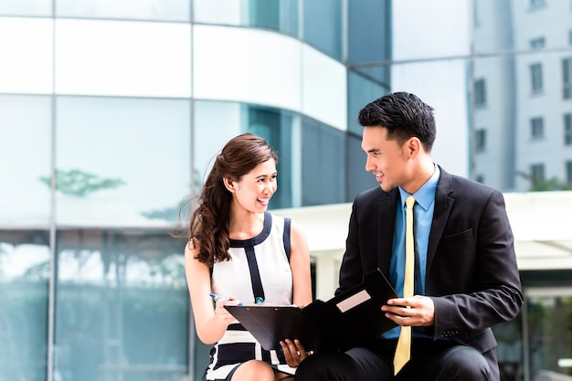 Asian business woman and man working outside signing contract or making notes