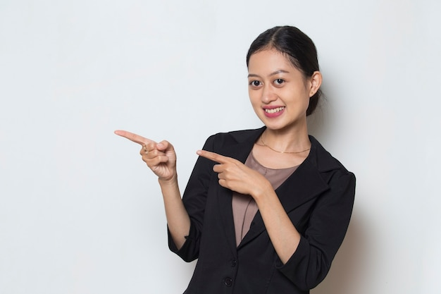 Asian business woman pointing with fingers to different directions copy space for advertisement