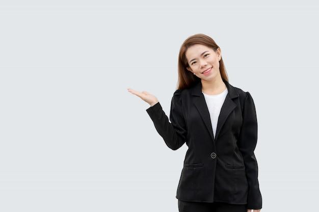 白い色に分離された黒のスーツで長い髪の手を提示するアジアビジネス女性