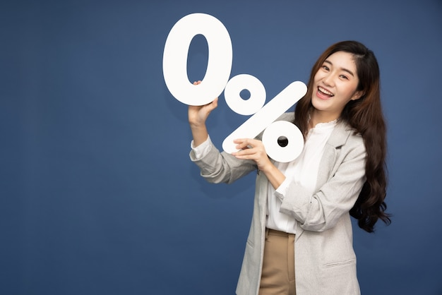 Азиатская деловая женщина показывает и держит 0% числа или ноль процентов, изолированных на темно-синей поверхности.