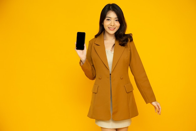 노란색 배경에 고립 된 손에 휴대 전화 응용 프로그램을 보여주는 아시아 비즈니스 여자