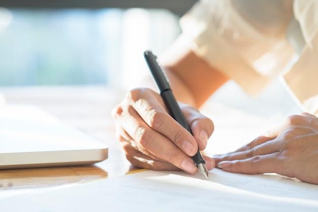 거래를 만드는 계약 문서에 서명하는 아시아 비즈니스 여자.