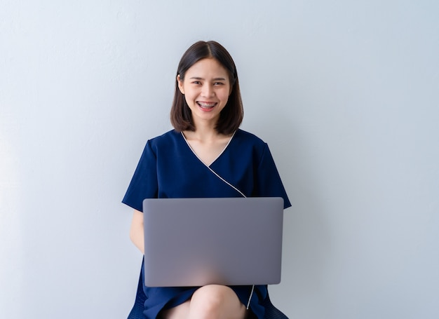 Asian business woman sitting on chair and using laptop in office home.