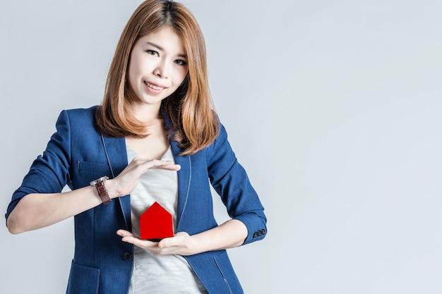 아시아 비즈니스 여자 미소 손 작은 집을 보호
