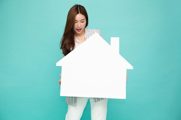 Азиатская деловая женщина улыбается и держит белый дом, изолированные на зеленом фоне