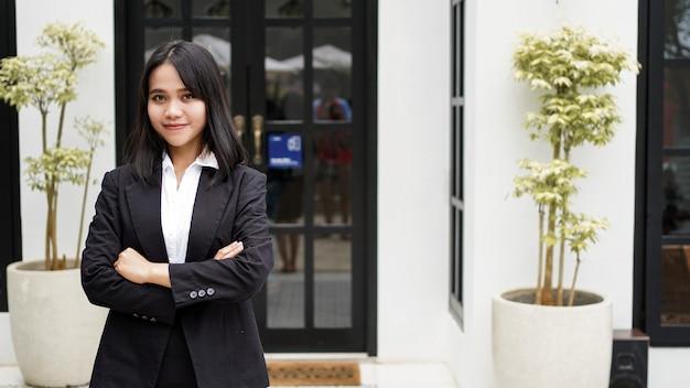 아시아 비즈니스 여자 웃 고 사무실 앞에 서