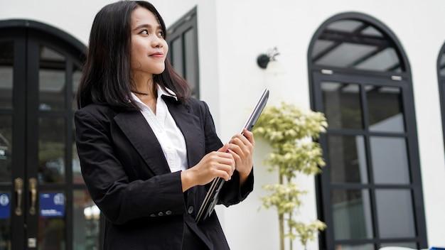 갈색 봉투와 함께 웃 고 사무실 앞에 서 아시아 비즈니스 여자
