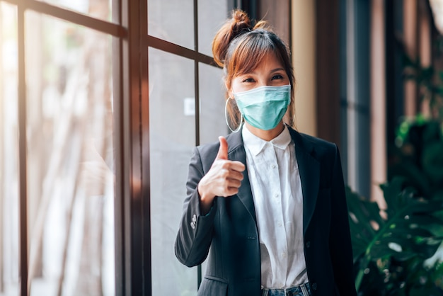 アジアビジネスの女性に立って、オフィスで親指を現しています。彼女はコロナウイルスまたはcovid-19の発生状況-ヘルスケアとビジネスコンセプトの予防でウイルス保護マスクを着ています。
