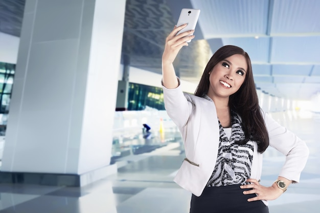 Asian business woman take selfie with her smartphone on the lobby, success people concept
