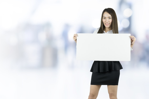Asian business woman taking blank whiteboard on blurred background.