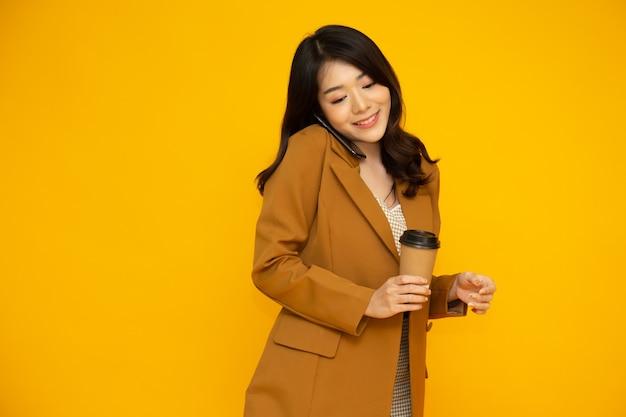 전화 통화와 뜨거운 커피 컵을 들고 아시아 비즈니스 여자