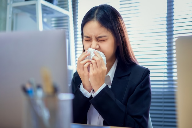 Asian business woman use paper napkin the mouth and nose because allergy in the table on office room.