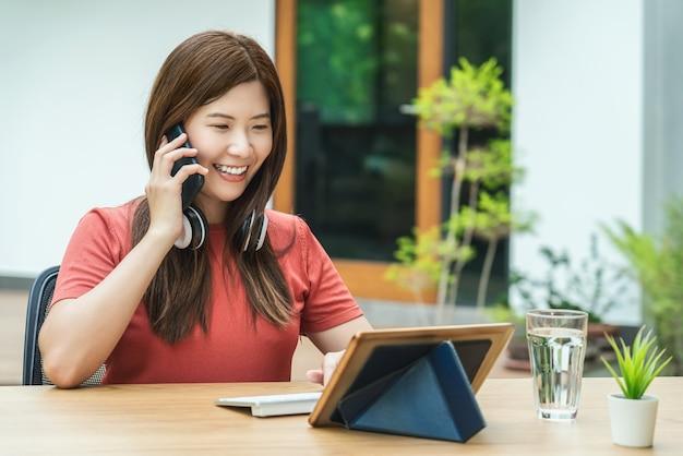 キーボード付きの携帯電話を使用し、在宅勤務を求めるアジアのビジネスウーマン