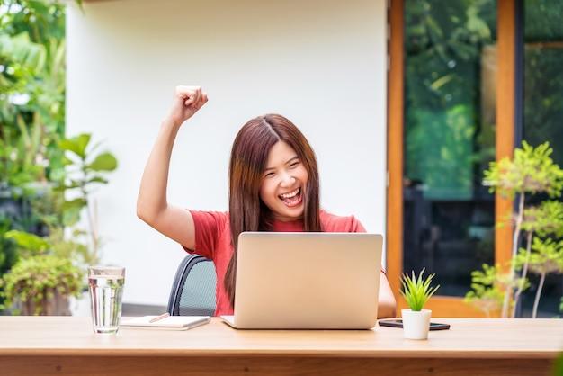 テクノロジーノートパソコンを使用し、仕事の成功が働くときに祝うアジアのビジネスウーマン