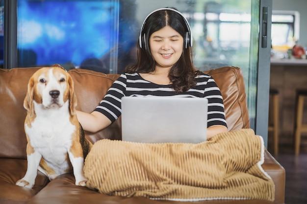 屋内の家で在宅勤務のための技術のラップトップとヘッドフォンを使用してアジアのビジネスウーマン