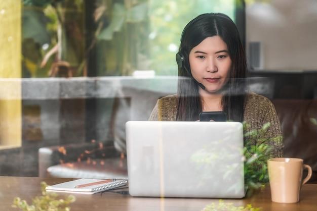 在宅勤務のための技術のラップトップとヘッドフォンを使用してアジアのビジネスウーマン