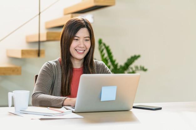 在宅勤務のための技術のラップトップと携帯電話を使用してアジアのビジネスウーマン