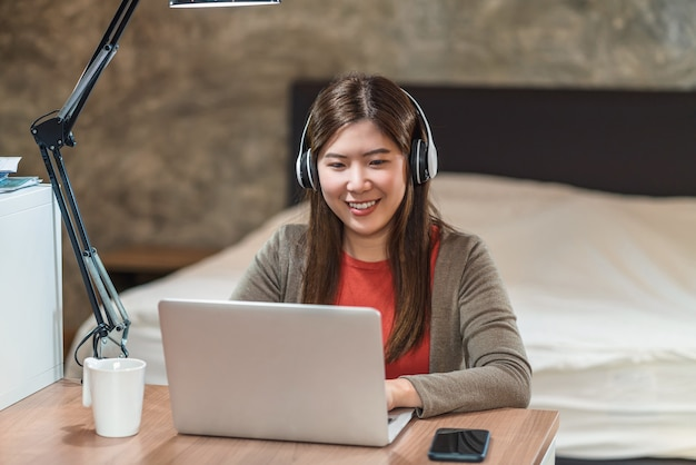 テクノロジーノートパソコンを使用し、寝室で自宅で仕事をしているアジアのビジネスウーマン
