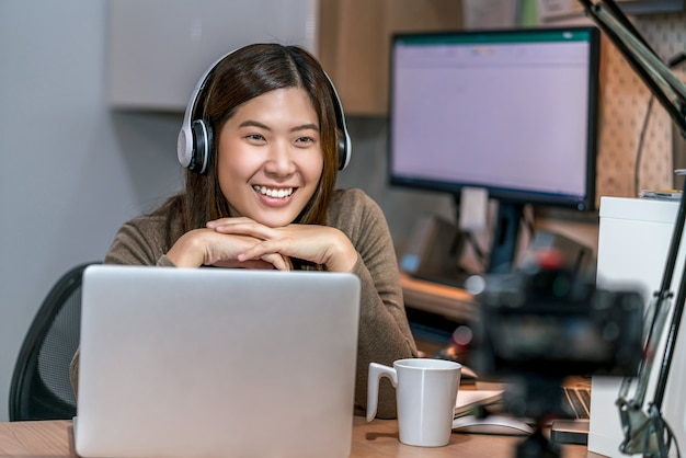 テクノロジーラップトップを使用して、ホームオフィスで在宅勤務のアジアのビジネスウーマン