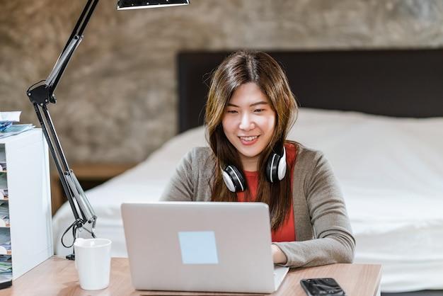 テクノロジーラップトップを使用して、屋内の寝室で自宅で仕事をしているアジアのビジネスウーマン